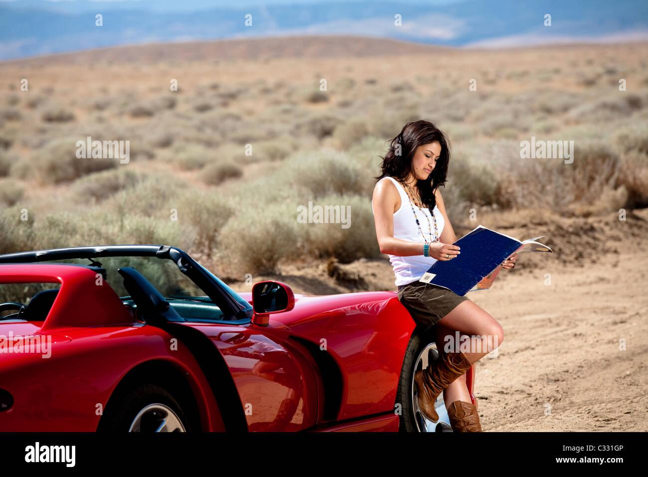 Una joven mujer atractiva lee un mapa mientras está de pie junto a un coche deportivo rojo en Lancaster, California. Imagen De Stock