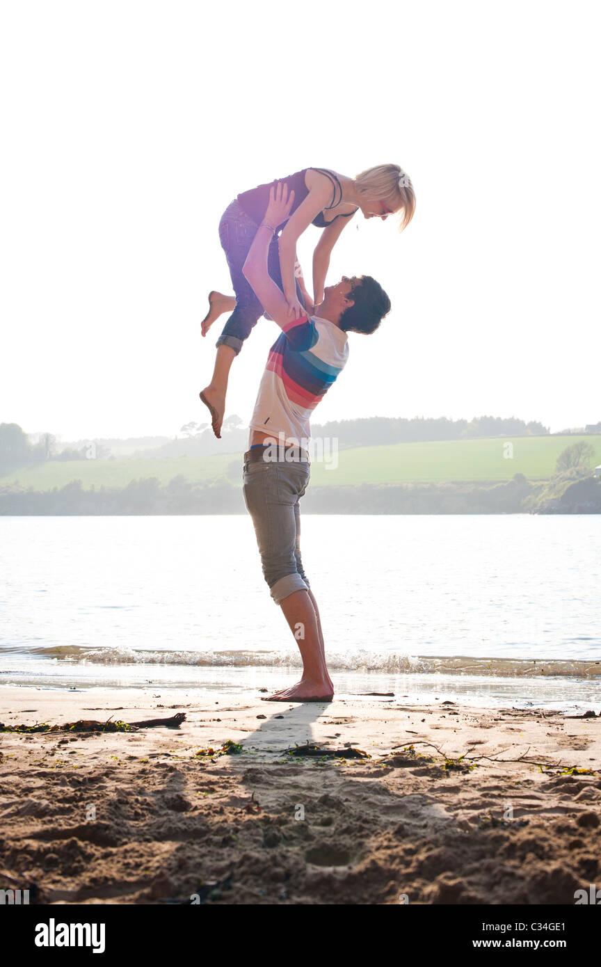 El hombre levantando chica de verano en la playa, amar Foto de stock