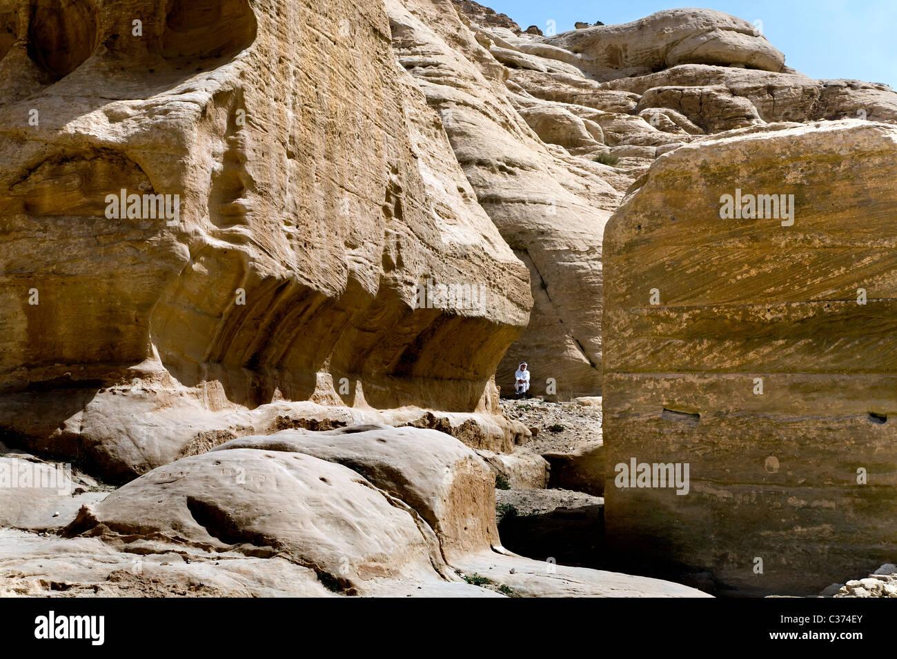 Un hombre jordano se encuentra entre las rocas de la rosa roja en la ciudad de Petra. Jordania Foto de stock