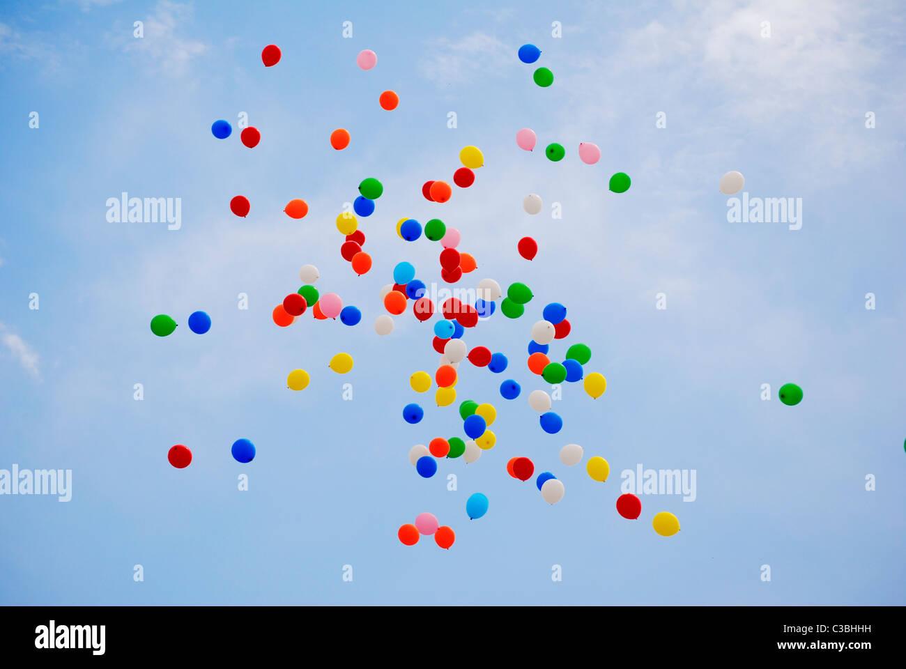Coloridos globos de helio liberado en el cielo azul en una celebración Imagen De Stock