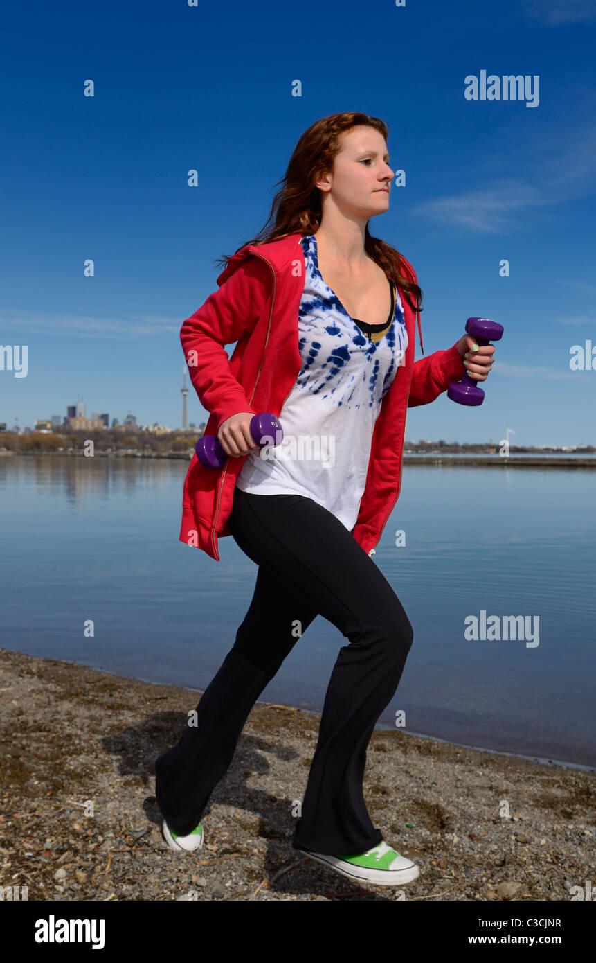 Adolescente corriendo por la orilla del lago Ontario en Toronto con pesas de mano contra el cielo azul Foto de stock