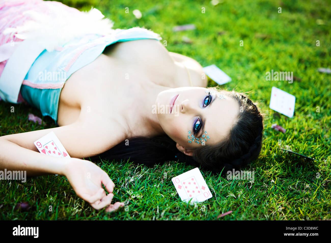 Misteriosa mujer joven con tarjetas en la hierba alrededor Foto de stock