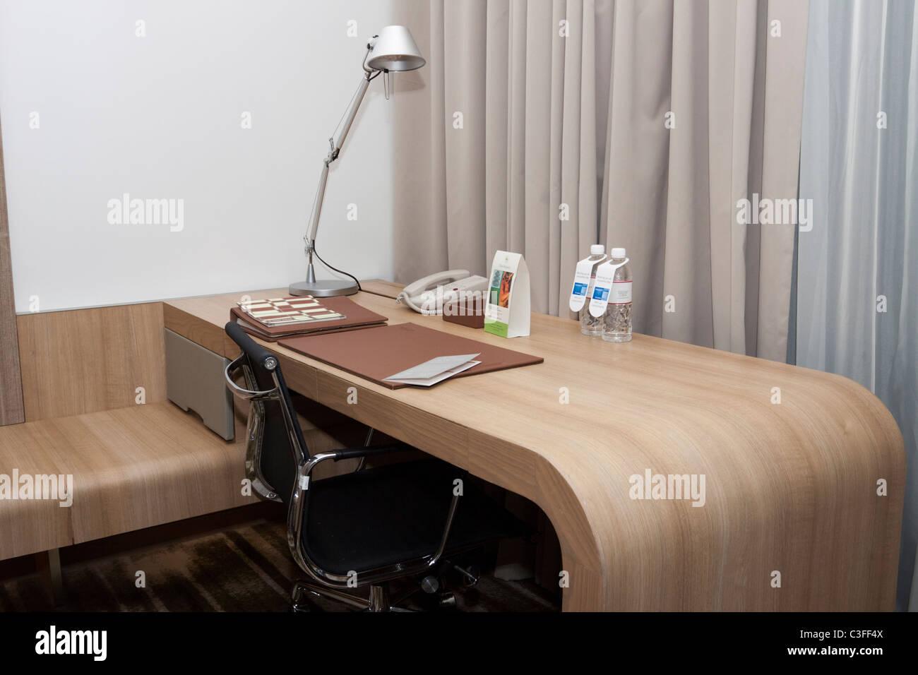 Business Desk en una habitación de hotel, mostrando la lámpara,teléfono,silla y botellas de agua. Imagen De Stock