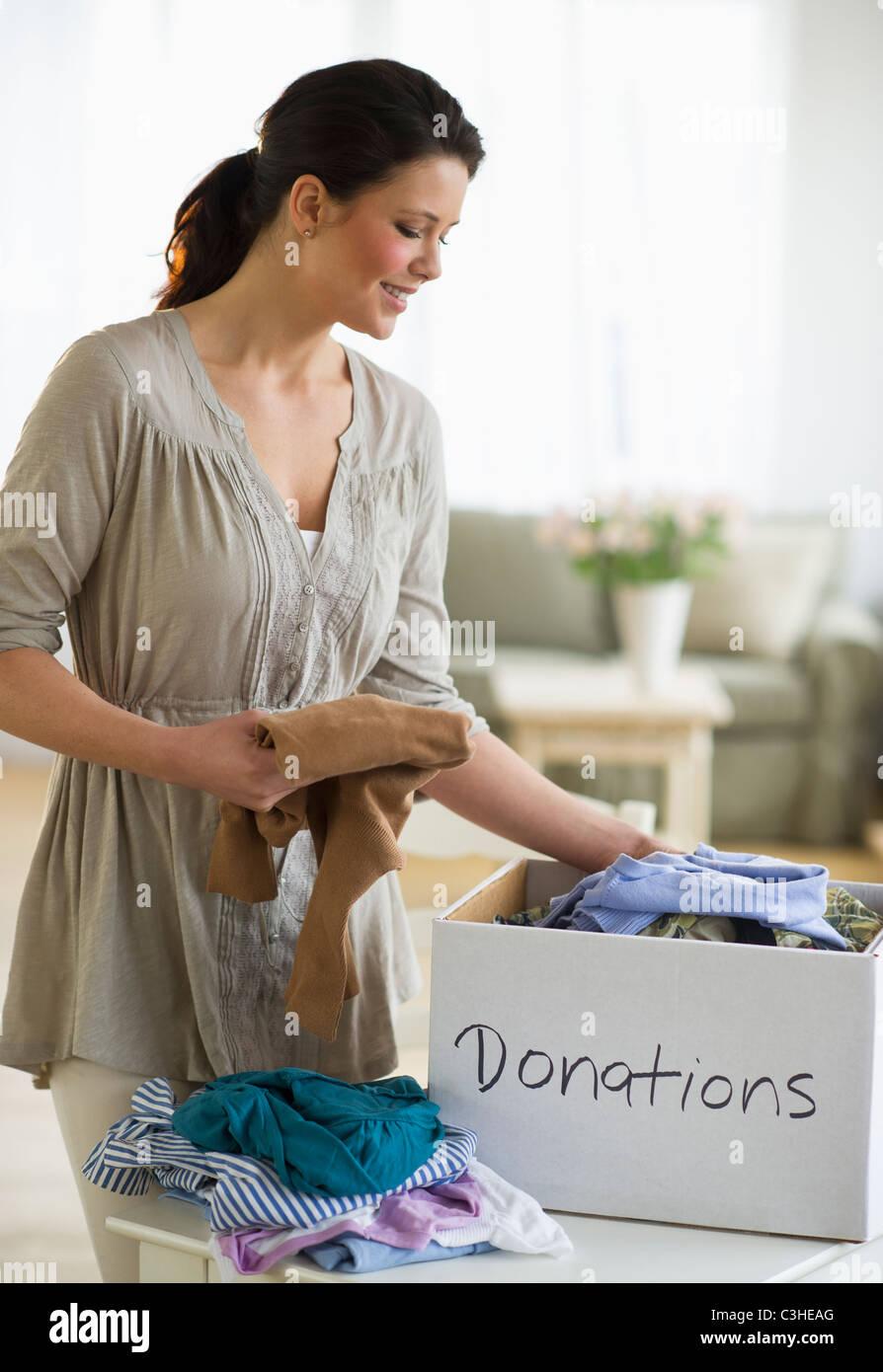 Mujer preparando ropa para donación Imagen De Stock