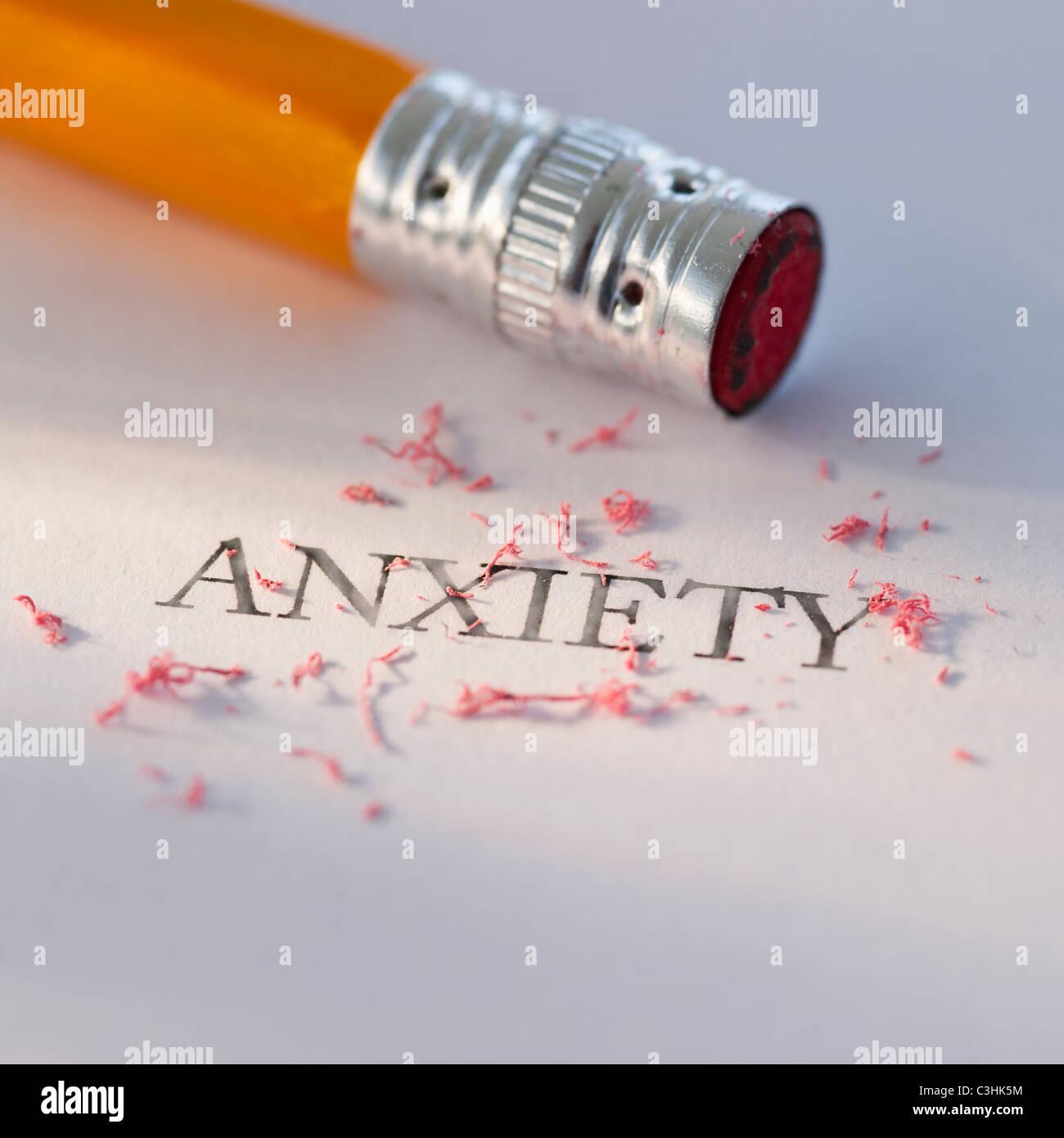 Foto de estudio de lápiz de borrar la palabra ansiedad de un pedazo de papel Foto de stock