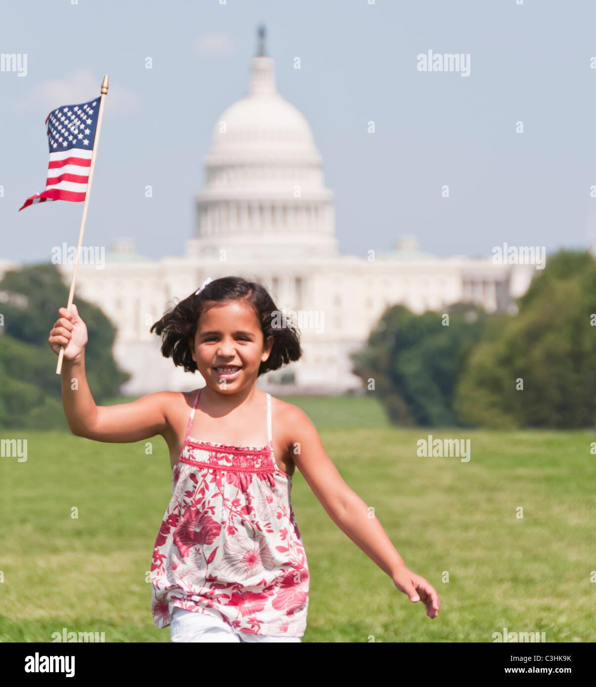 Ee.Uu., Washington DC, chica (10-11) con bandera estadounidense corriendo delante del edificio del Capitolio Imagen De Stock