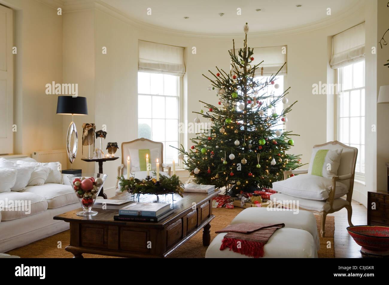 Árbol de navidad decorado con bolas en Regency salón con sillones y velas Imagen De Stock