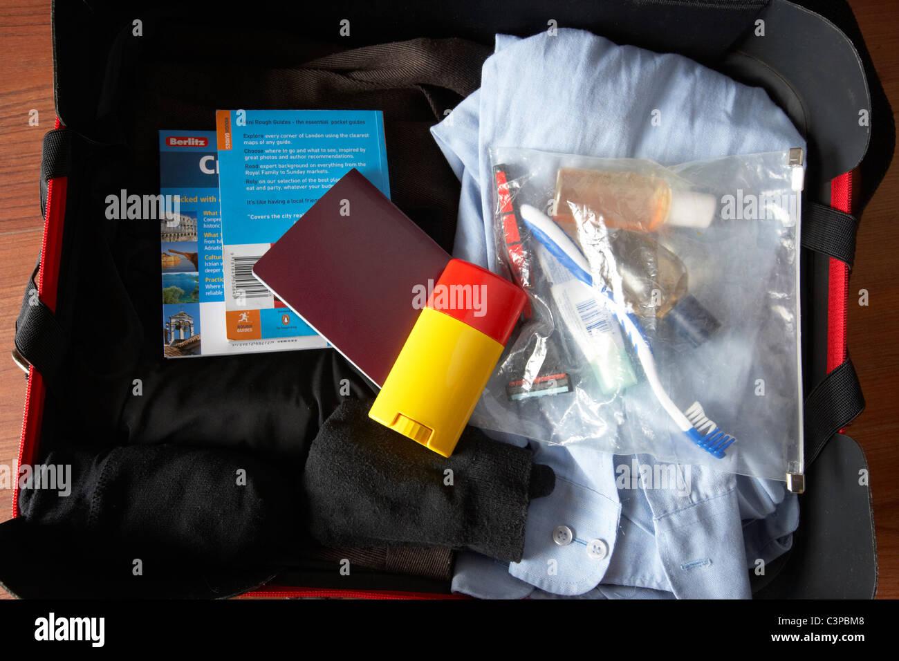 Equipaje para un viaje de negocios incluyendo el pasaporte y artículos de tocador en ver a través de una Imagen De Stock