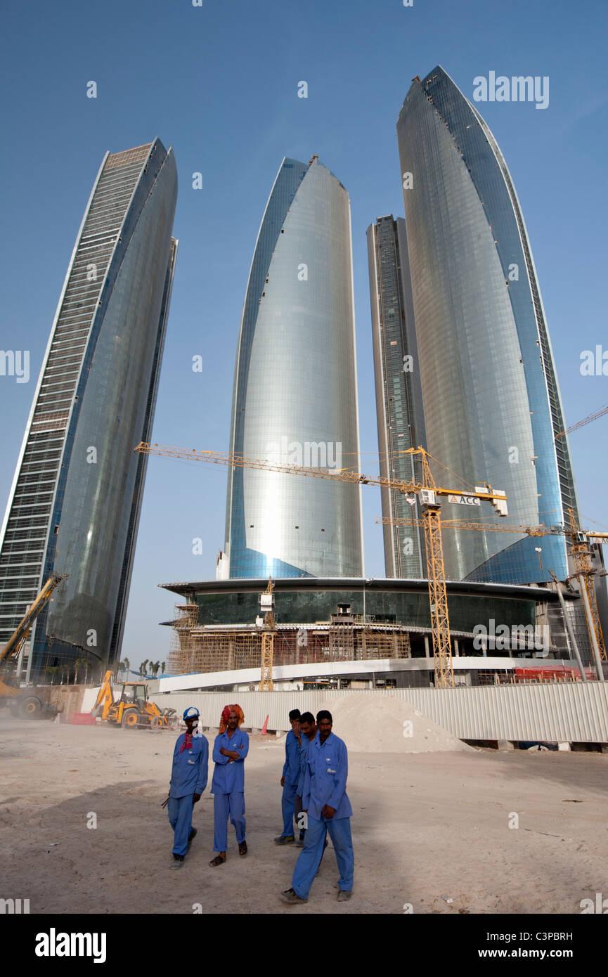 Los trabajadores de la construcción en el sitio de construcción de nuevos rascacielos Etihad Towers en Imagen De Stock