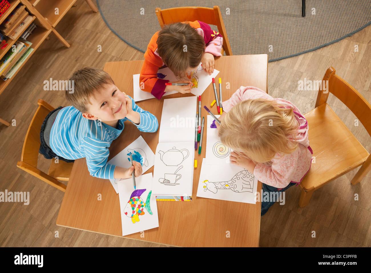 Alemania, niños en vivero sentado en la tabla dibujando, niveles elevados de ver Imagen De Stock