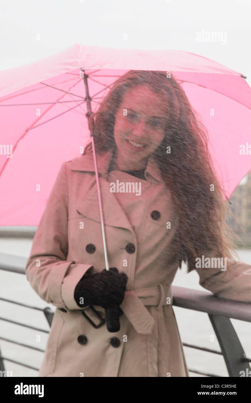 Mujer joven con paraguas en la lluvia Foto de stock