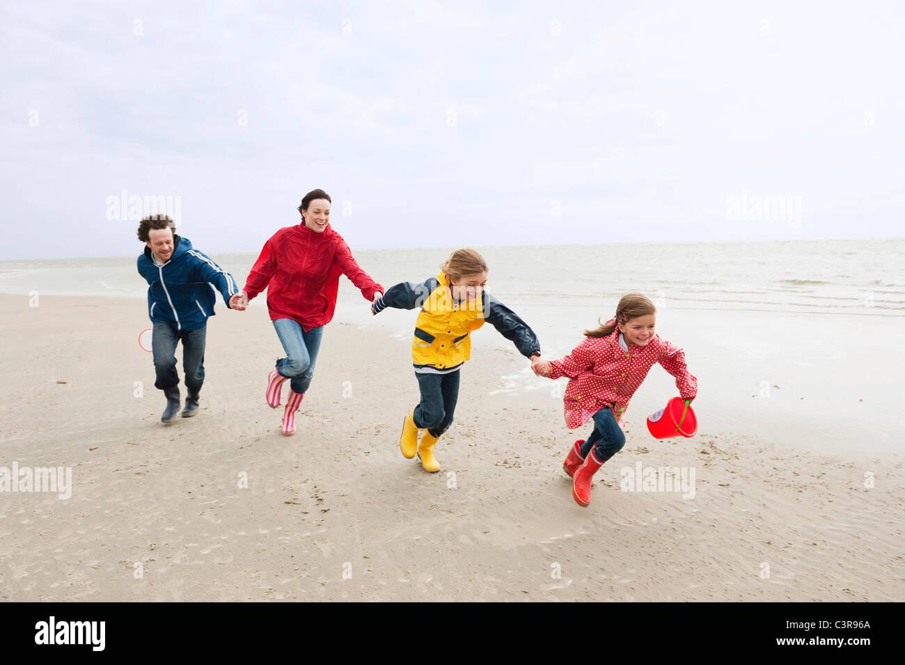 Alemania, St. Peter-Ording, Mar del Norte, la familia tomados de la mano y corriendo en la playa Imagen De Stock