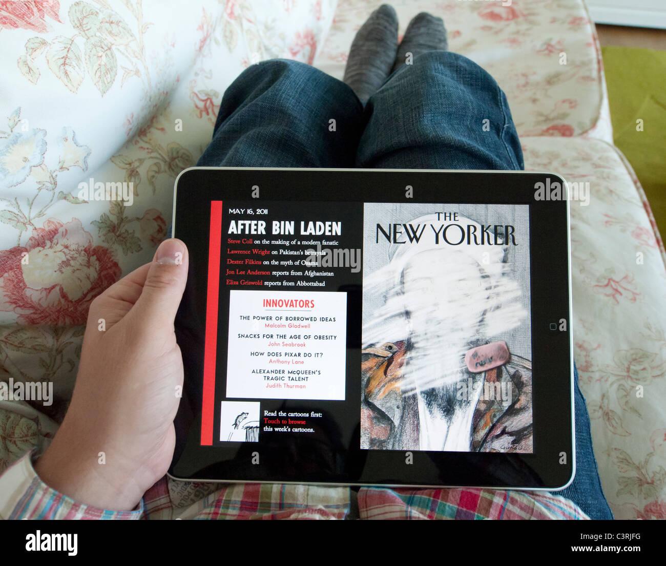 Hombre leyendo iPad versión digital de la revista New Yorker Foto de stock