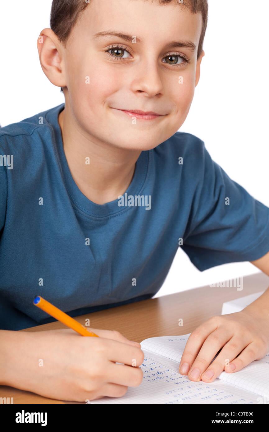 El colegial haciendo sus deberes en su escritorio Imagen De Stock