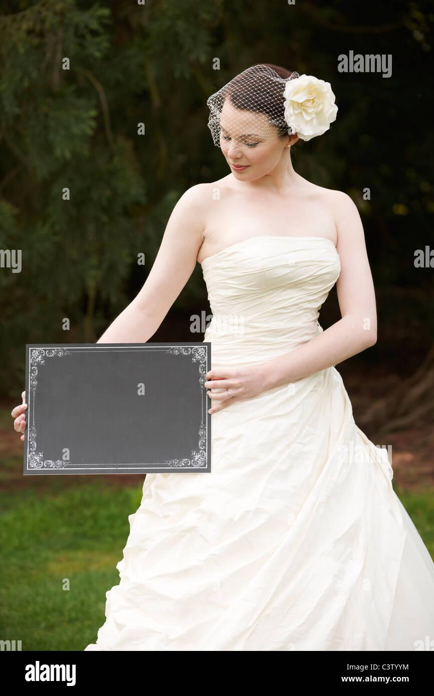 Bonito vestido de novia novia en la celebración de una junta con el espacio en blanco para copiar Foto de stock