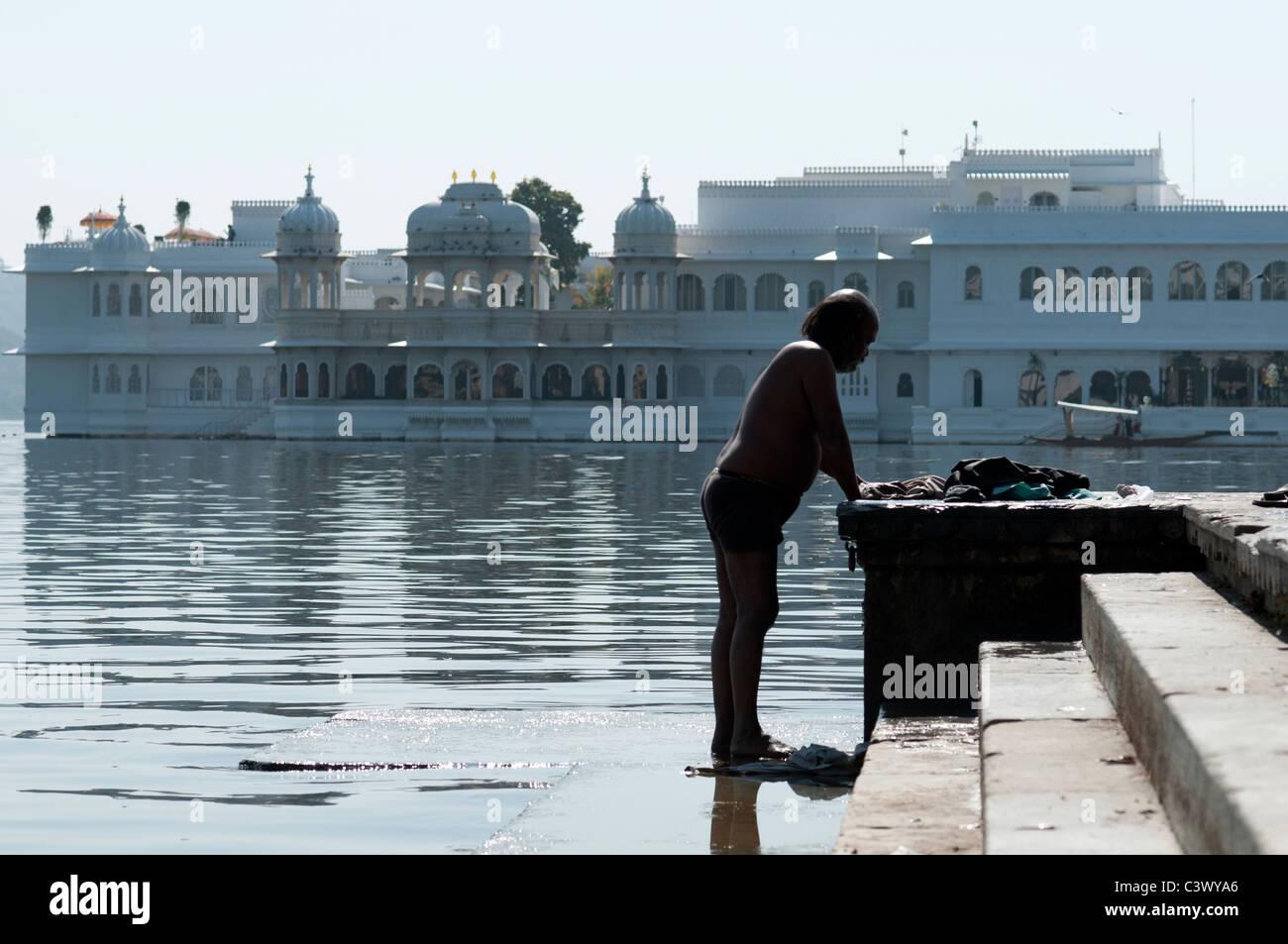 Hombre lavando su ropa en frente del palacio de Udaipur. Imagen De Stock