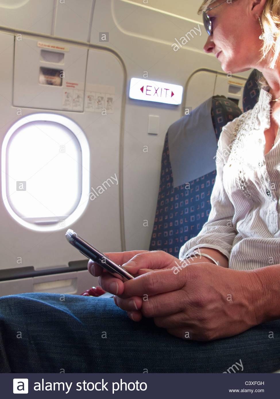 Cerca de la mujer la mensajería de texto del teléfono celular en el avión Imagen De Stock