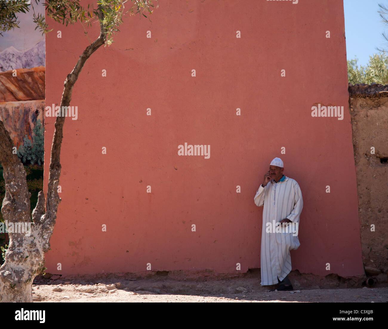 Hombre de pie junto a una pared de ladrillo rojo Kelaa M'Kouna Foto de stock