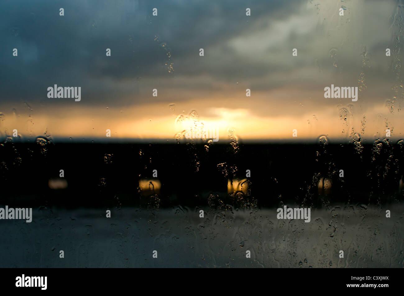 La lluvia sobre el cristal de coche al atardecer en noche tormentosa Imagen De Stock