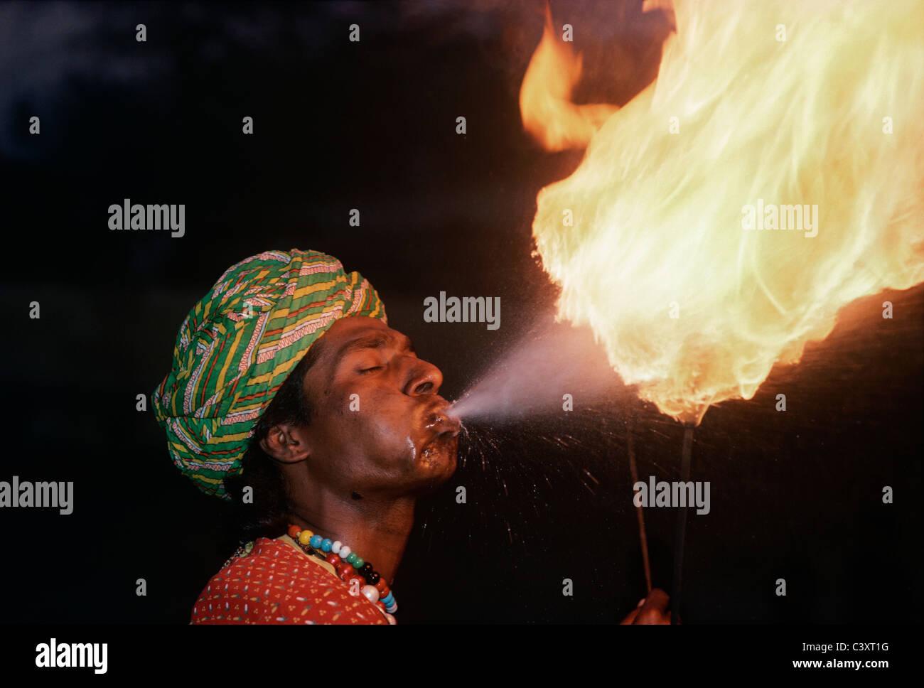 Indian tragafuegos sopla las llamas durante un espectáculo de calle. Nueva Delhi, India Imagen De Stock
