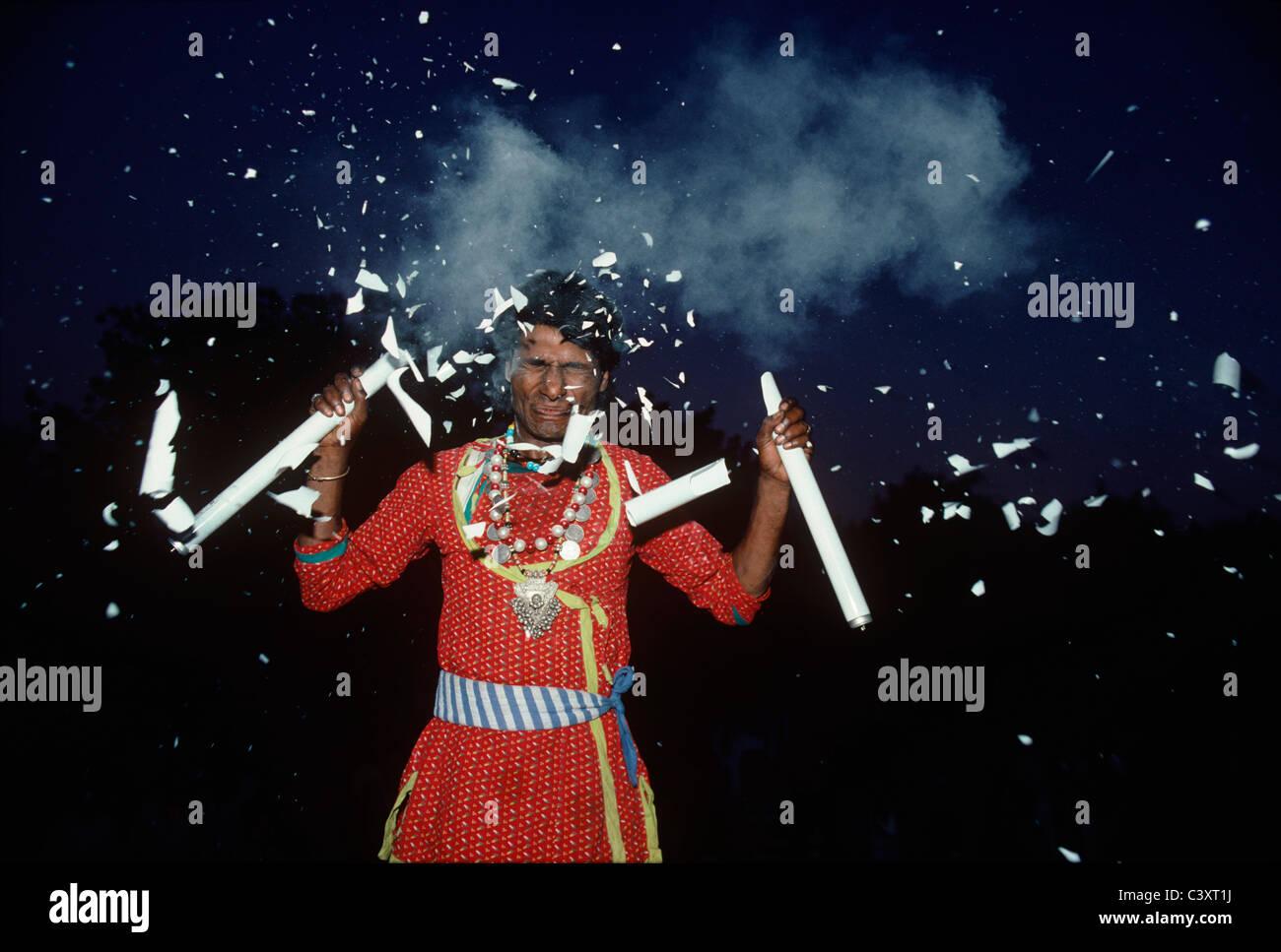 Indian Street Performer rompe bombillas en su cabeza. Nueva Delhi, India Imagen De Stock