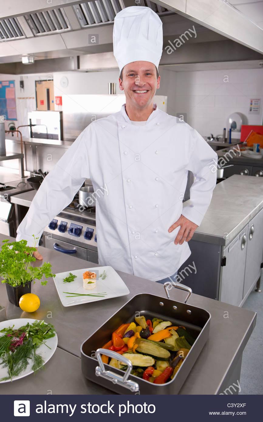 Chef sonriente de pie con verduras en cocina comercial Imagen De Stock