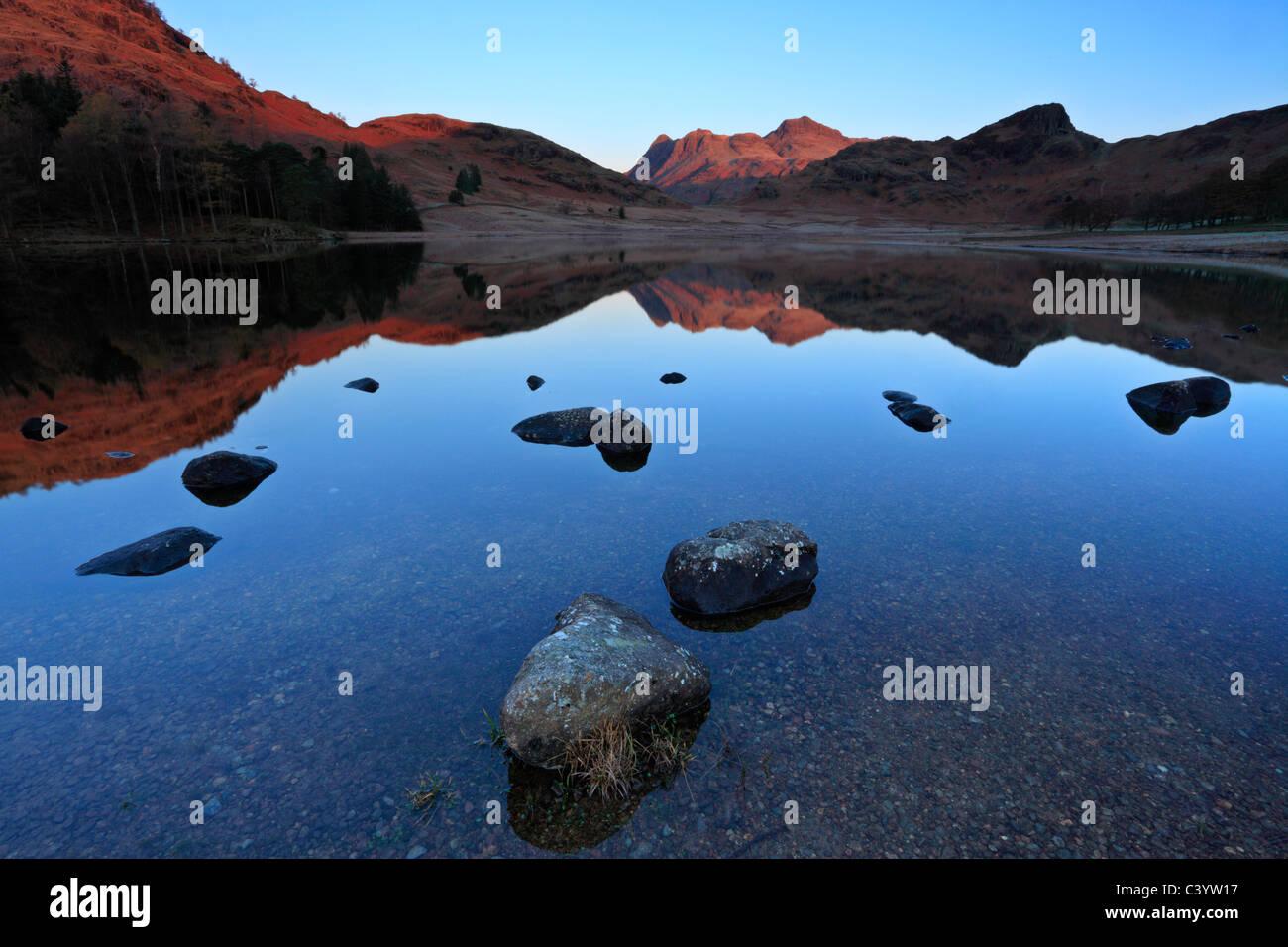 A finales de otoño la luz sobre el hielo de los bordes de una calma Blea Tarn, en el distrito de los lagos Imagen De Stock