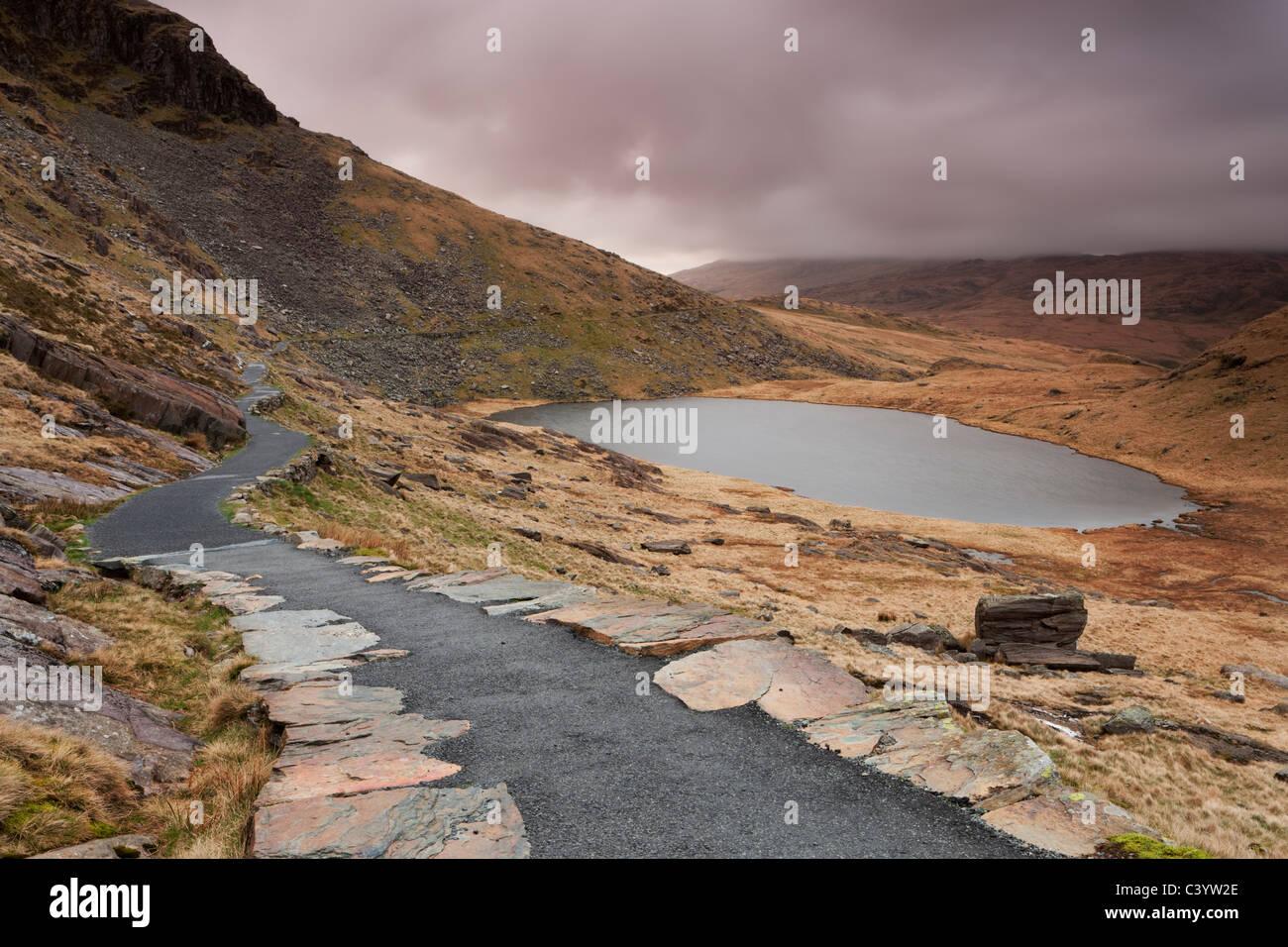 Los mineros vía sendero sinuoso alrededor de Llyn Teyrn en el descenso del monte Snowdon, Snowdonia Imagen De Stock