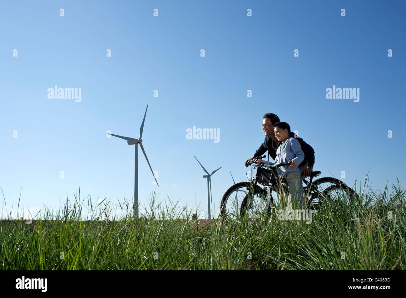 Padre e hijo con bicicletas por un parque eólico Foto de stock