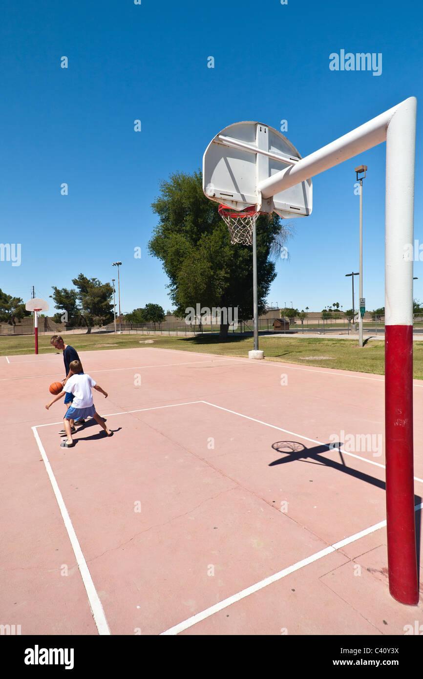 Muchachos jugando baloncesto en un parque del barrio en el exterior Imagen De Stock