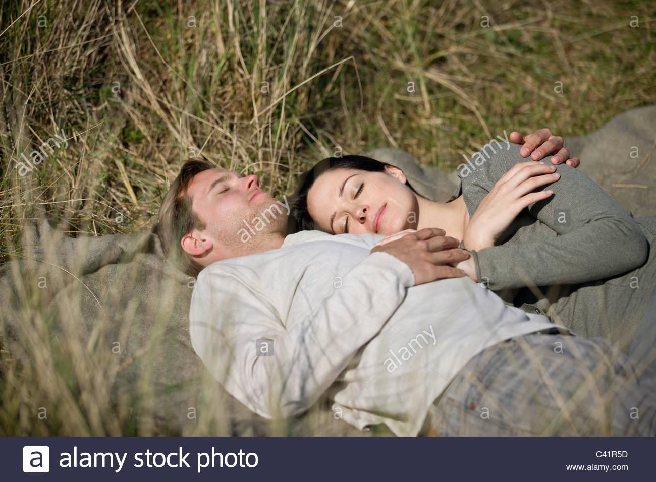 Una mujer embarazada y su pareja durmiendo en entre Pasto largo Imagen De Stock