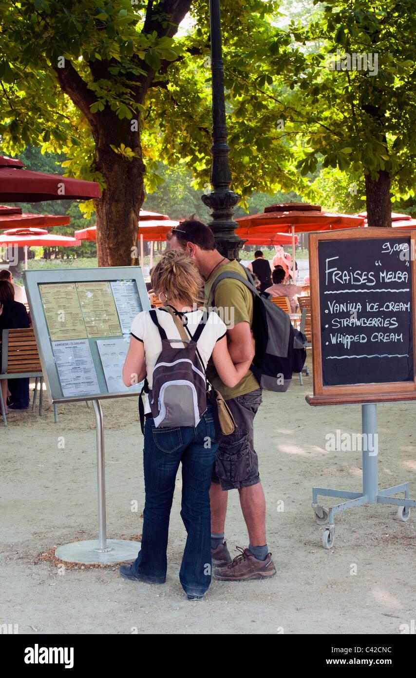 Pareja mirando el menú junta en Café al aire libre en el Jardin du Tuilleries Foto de stock