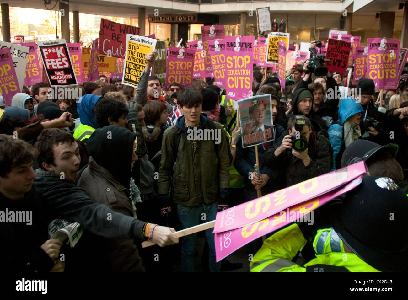 Un policía golpea con una pancarta durante la primera protesta estudiantil en Londres en noviembre de 2010. Imagen De Stock