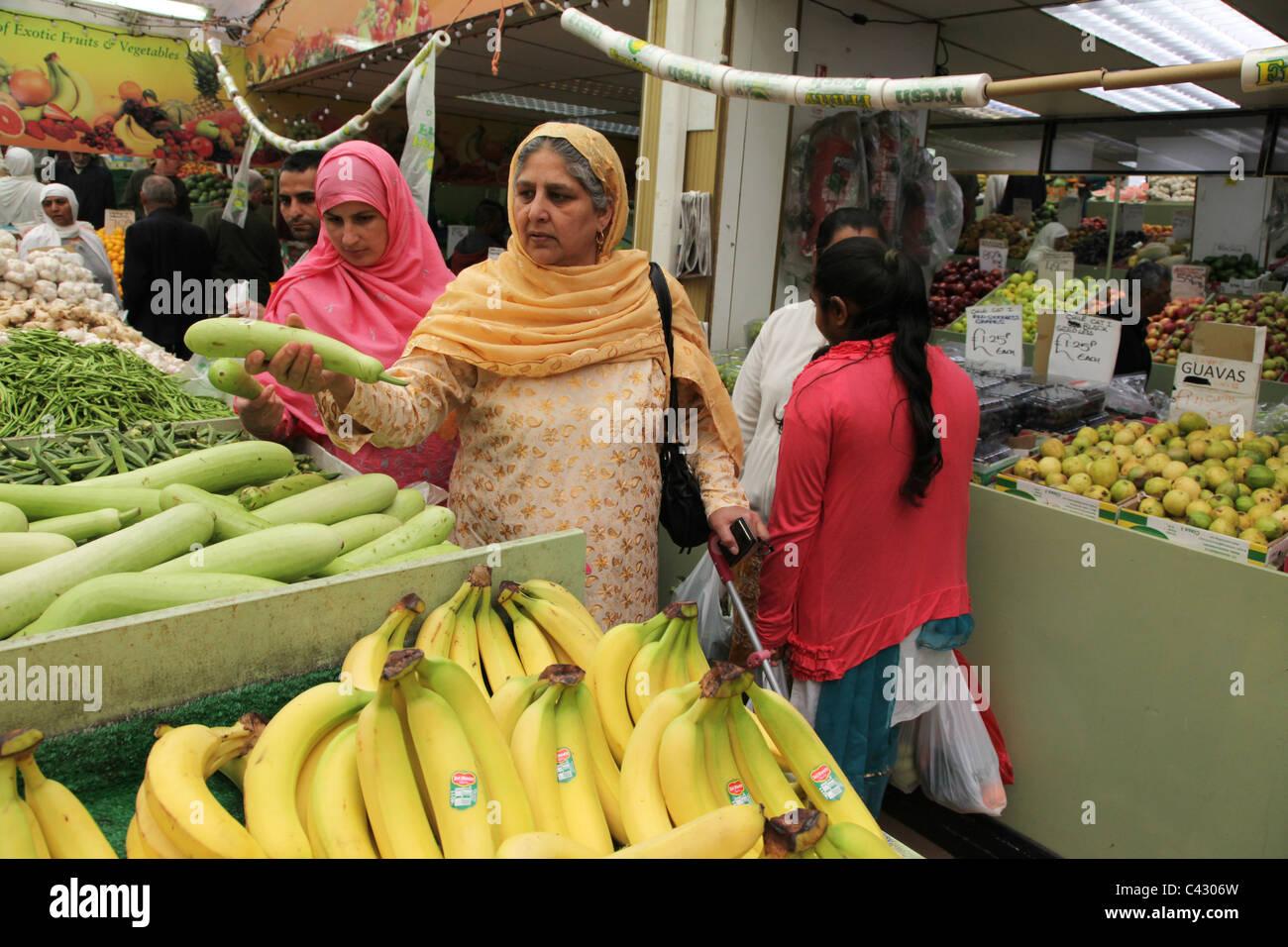 Las mujeres asiáticas, hurgando para frutas y verduras en una tienda en Wembley. El centro de la ciudad tiene una Foto de stock