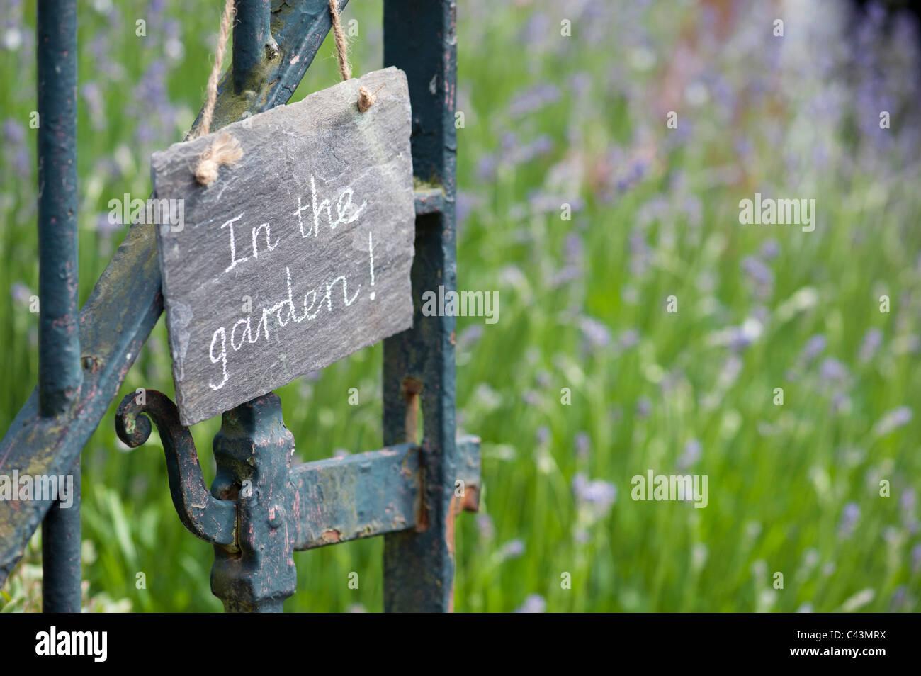 """""""En el jardín"""", escrito con tiza en la pizarra, colgado en la puerta de un jardín inglés. Imagen De Stock"""