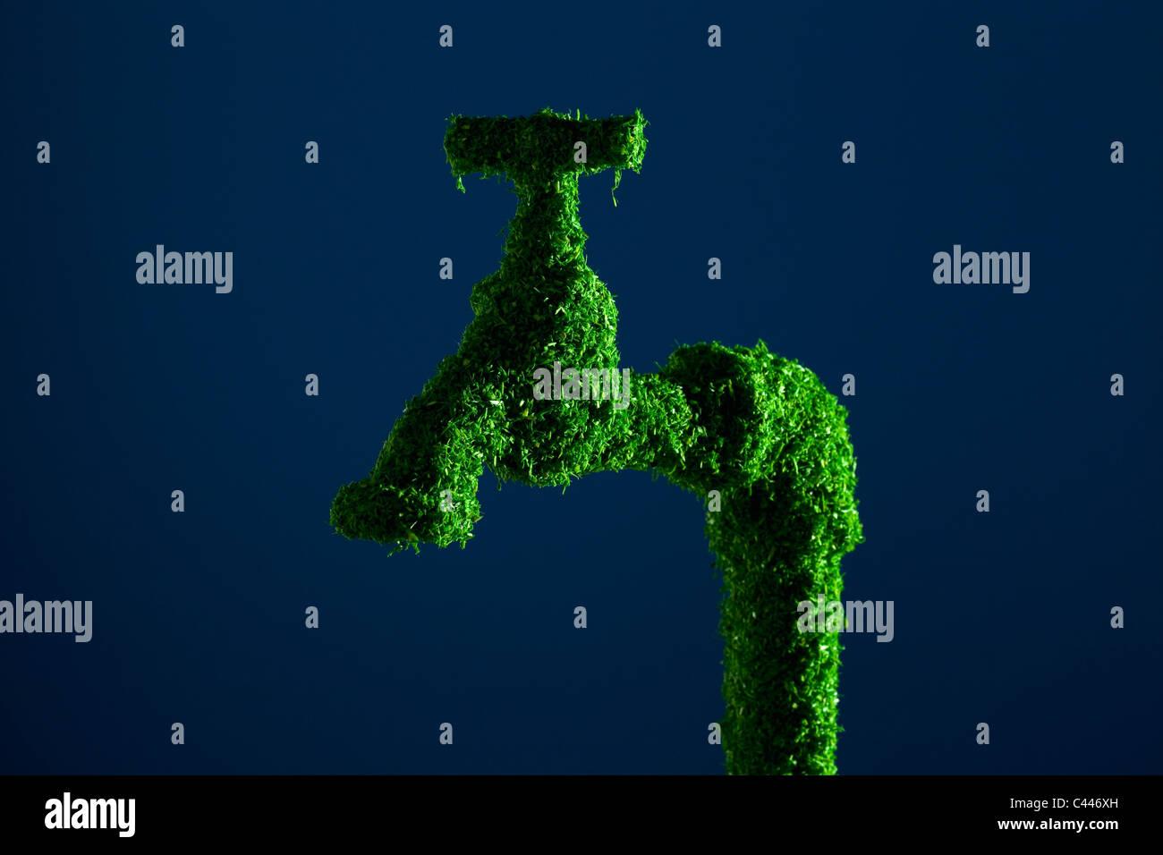 Grifo de agua energía verde cubierto de hierba Imagen De Stock