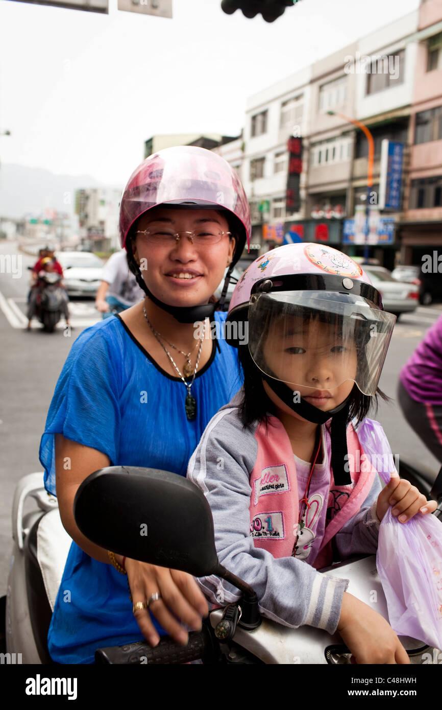 Madre e hija retrato en scooter, Taipei, Taiwán, 23 de octubre de 2010. Imagen De Stock