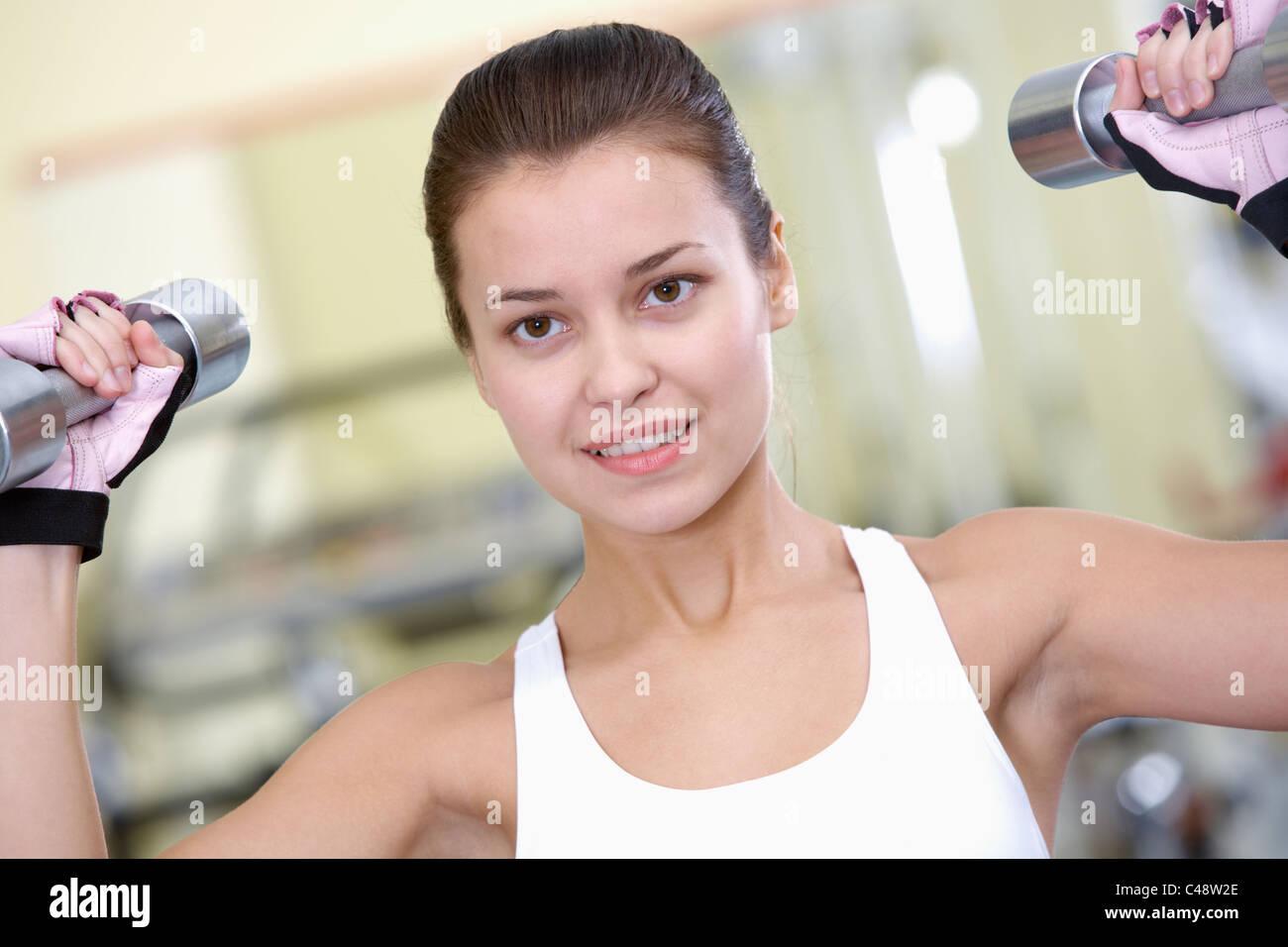Retrato de mujer joven haciendo ejercicios con pesas en el gimnasio Imagen De Stock