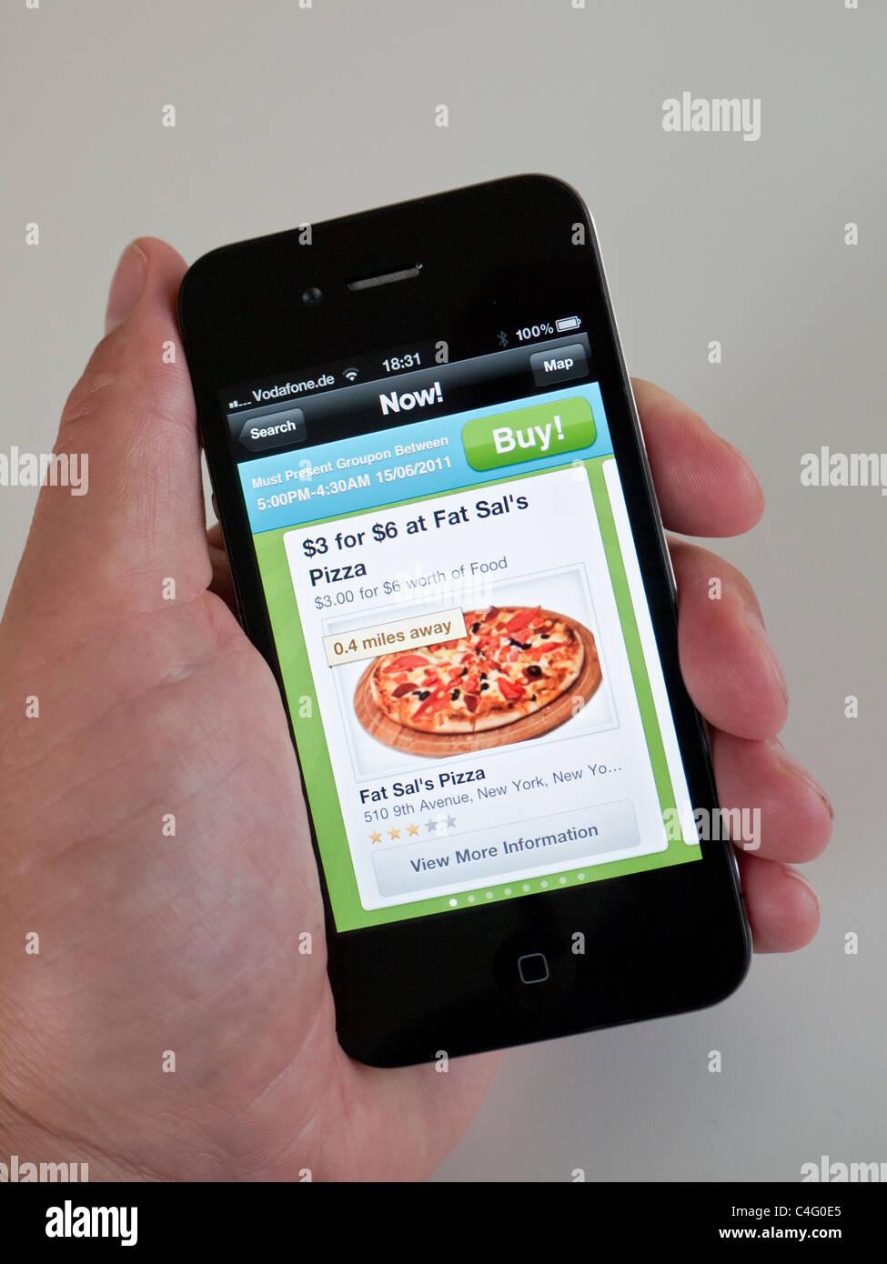 Utilizando app Groupon para buscar cosas sobre la pizza en la Ciudad de Nueva York en el iPhone 4G teléfono Imagen De Stock