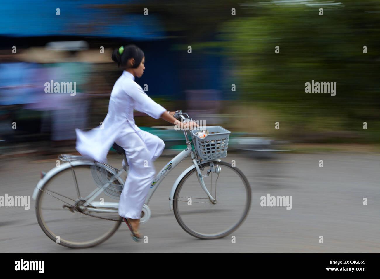 Una niña de Ao Dai en una bicicleta, el delta del Mekong, Vietnam Imagen De Stock