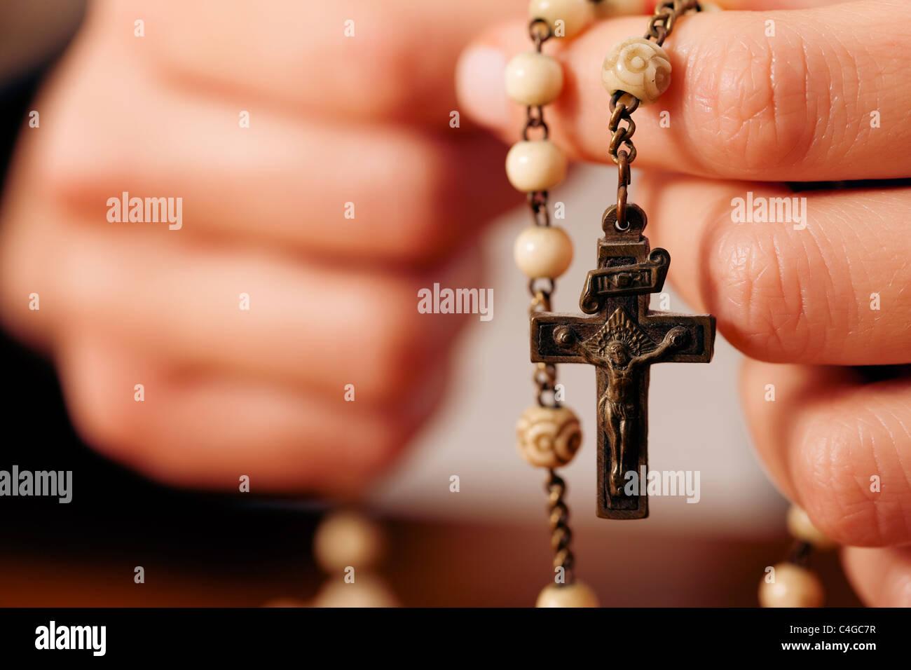 Mujer (sólo cerca de manos para ser visto) con Rosario enviar una oración a Dios, la configuración Imagen De Stock