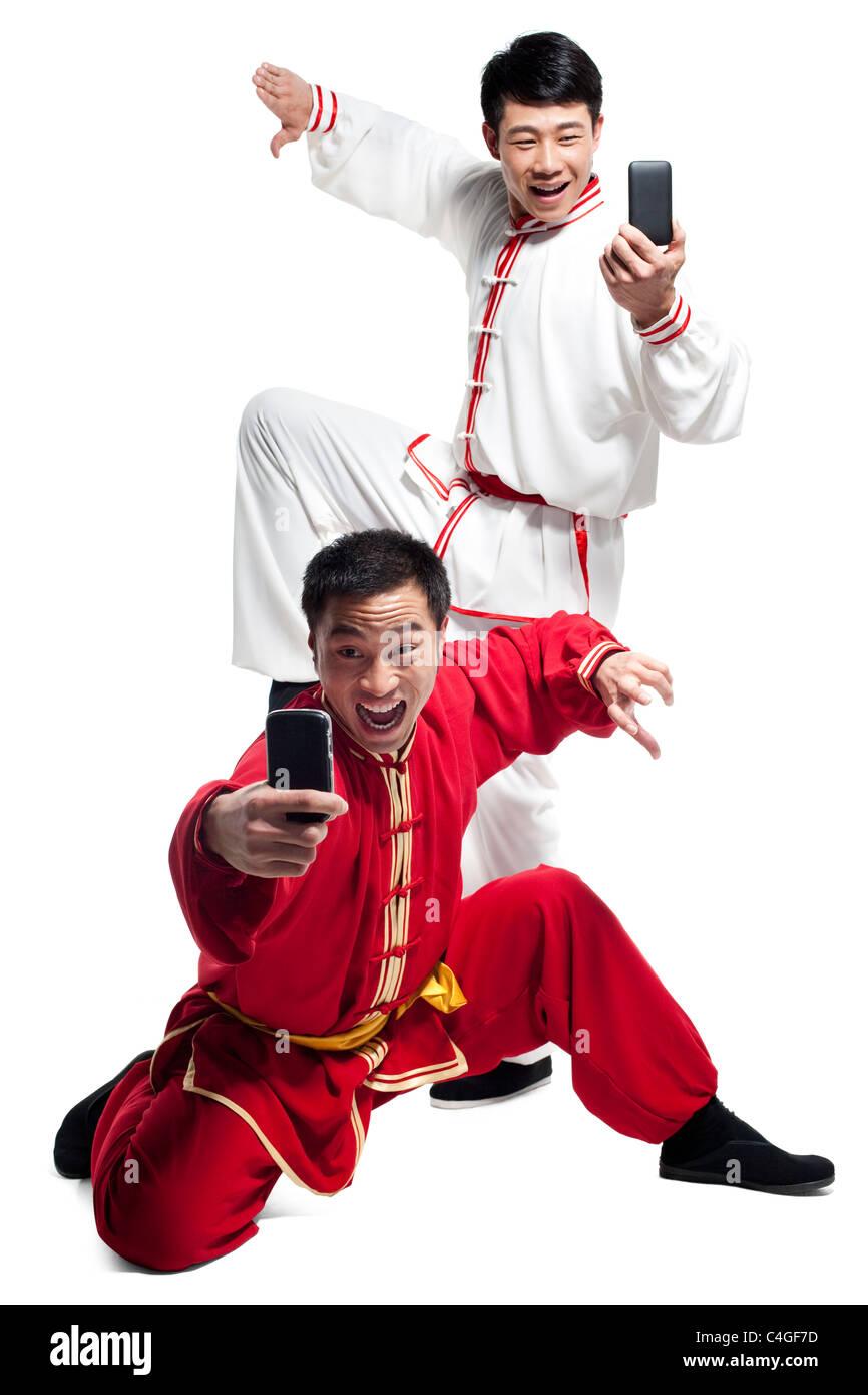 Los hombres haciendo artes marciales y mirando al teléfono móvil Foto de stock