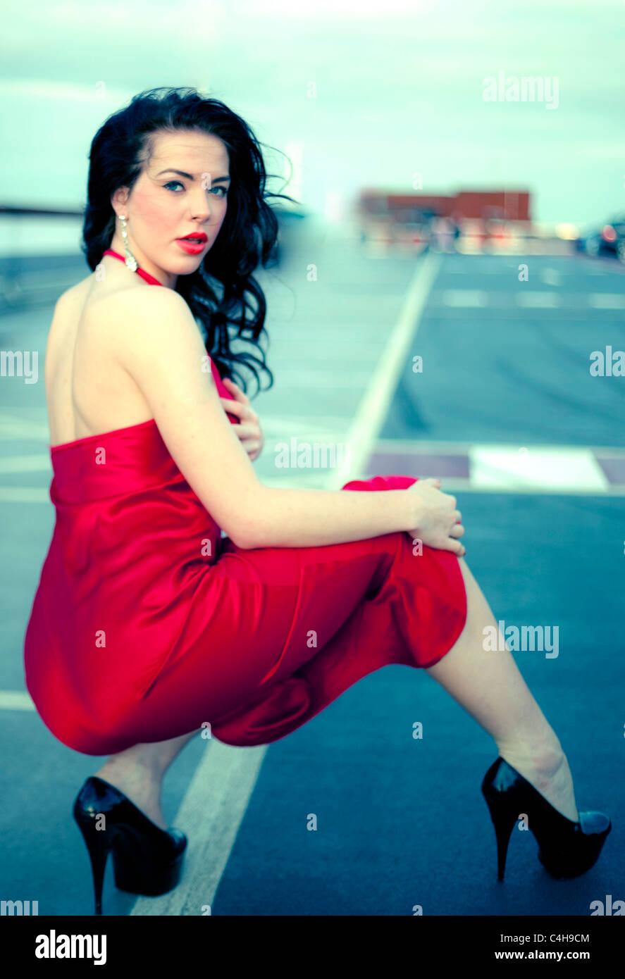 Bella mujer en cuclillas con tacones y llevaba un vestido rojo, Londres, Inglaterra, Reino Unido. Imagen De Stock