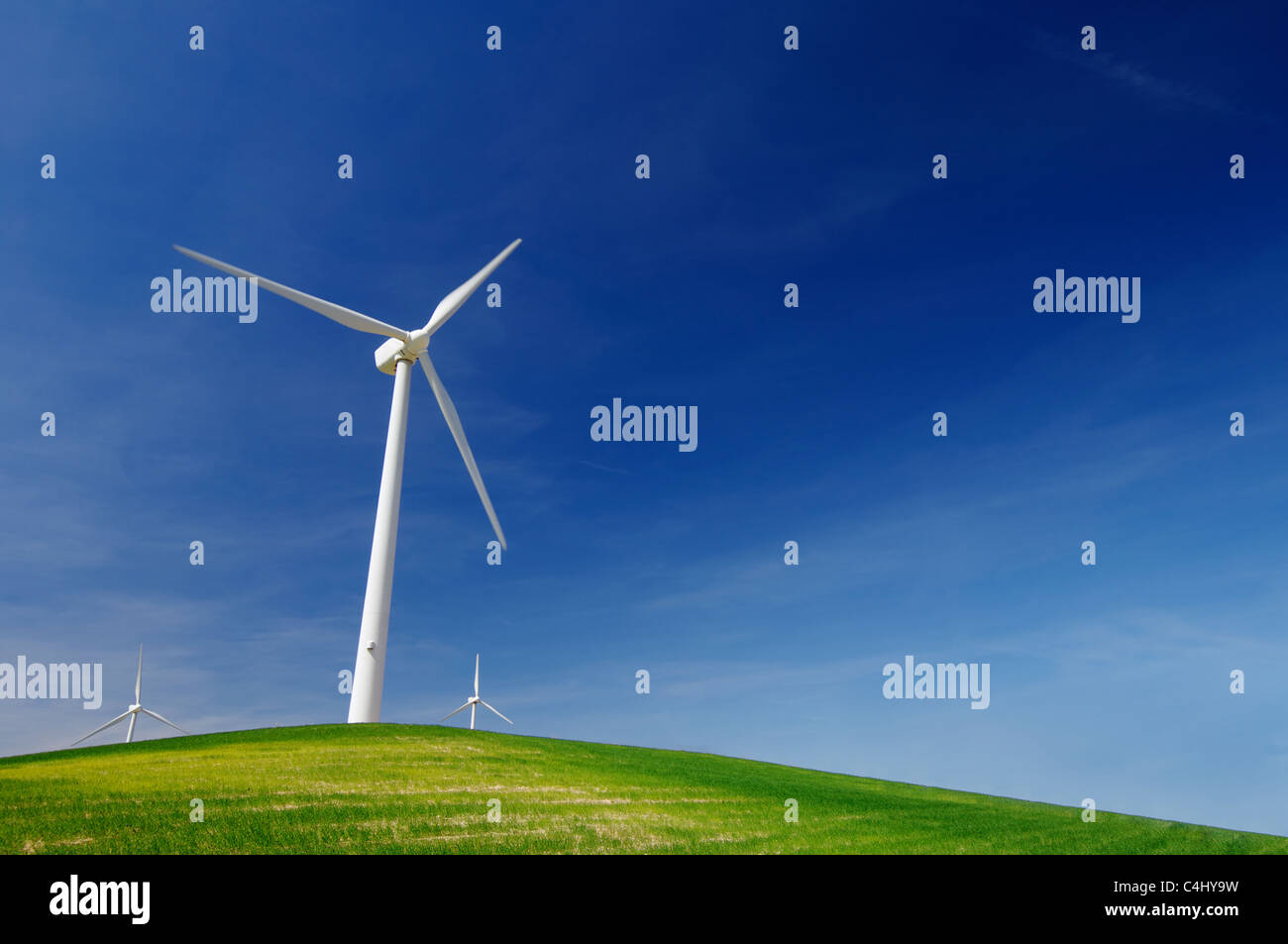 Molinos de viento en una colina verde con cielo azul Imagen De Stock