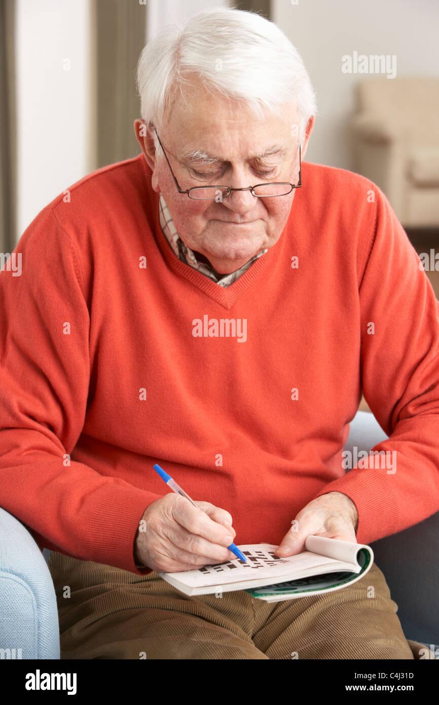 5a10d30a5772c Hombre senior en la silla relajante en casa completando Crucigramas Imagen  De Stock