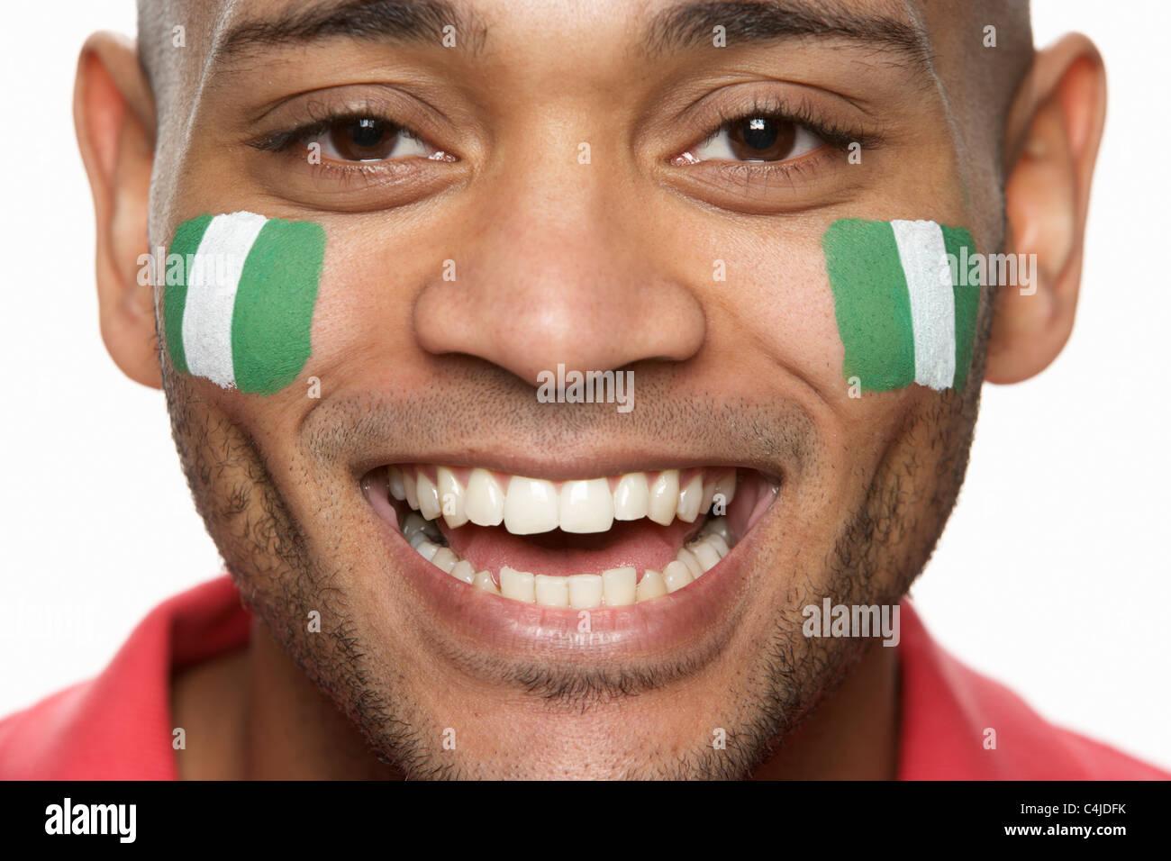 Macho joven hincha con bandera nigeriana pintado en la cara Foto de stock