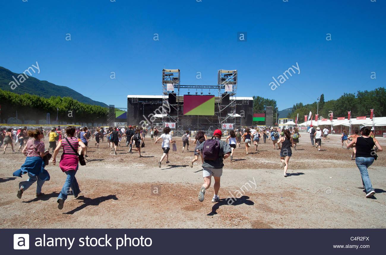 Los jóvenes funcionando para ver su banda favorita en Musilac Festival de música pop rock en verano Imagen De Stock