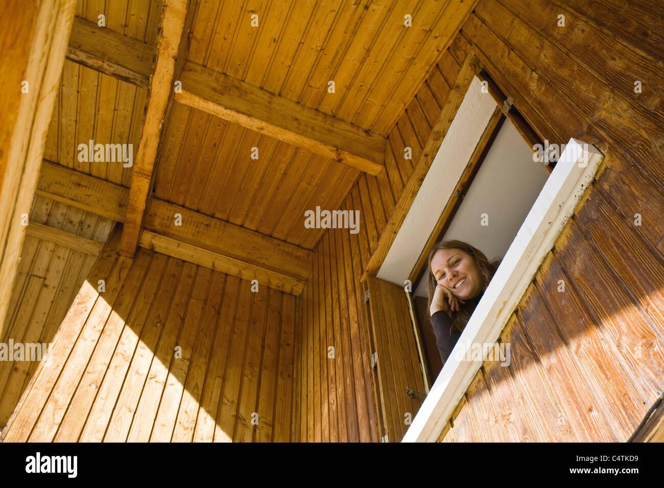 Mujer mirando por la ventana, mirando a la cámara Imagen De Stock