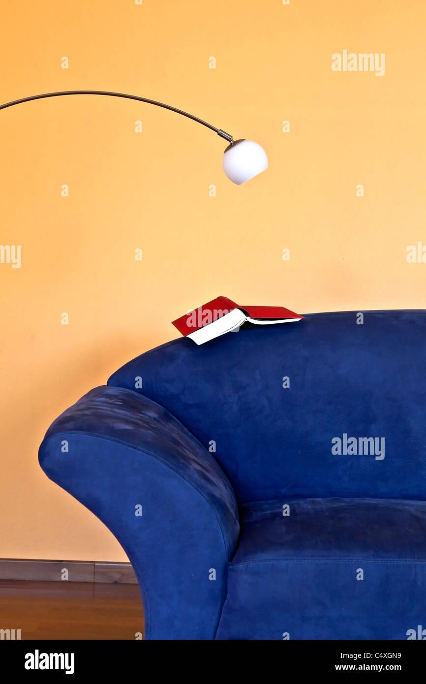 Un rincón de lectura con un sofá azul, un libro y una lámpara de lectura Imagen De Stock