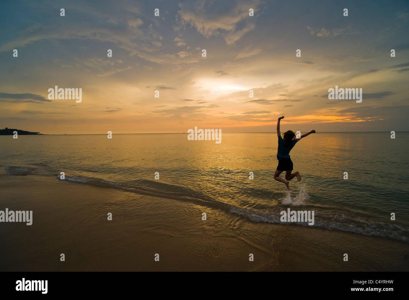 Una joven salta de alegría y celebración en la playa al atardecer. Tomada en Phra Ae Beach, Koh Lanta, Imagen De Stock